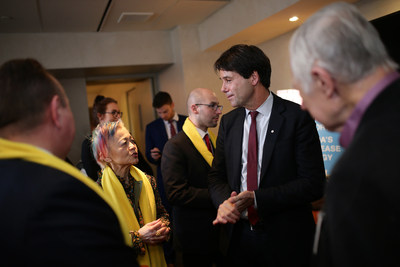 Ontario Health Minister Eric Hoskins speaking with Durhane Wong-Rieger, President and CEO of the Canadian Organization for Rare Disorders, at Queen's Park on International Rare Disease Day.